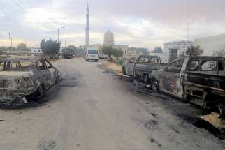 Damaged vehicles are seen Nov. 25 after a bomb attack at Al-Rawdah Mosque in Bir al-Abd, Egypt.
