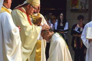 Cardinal Thomas Collins lays his hands on the head of newly ordained Bishop Robert Kasun.  Kasun was ordained a bishop Sept. 12 in Edmonton and will be an auxiliary bishop of Toronto.