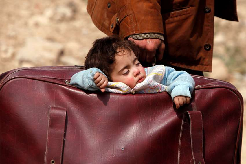 A child sleeps in a suitcase in Beit Sawa, Syria, March 15.
