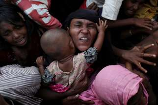 A Rohingya woman holds her infant as she scuffles to receive relief aid Nov. 28 in the Kutupalong refugee camp near Cox's Bazar, Bangladesh.