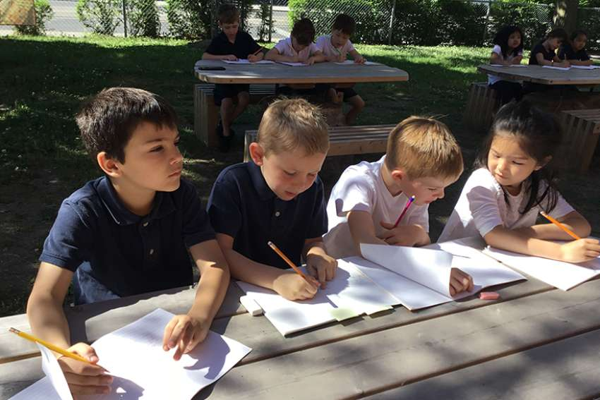 Students learn outside for a class with their teacher, Tralee Reford, at St. John's Catholic Elementary School.