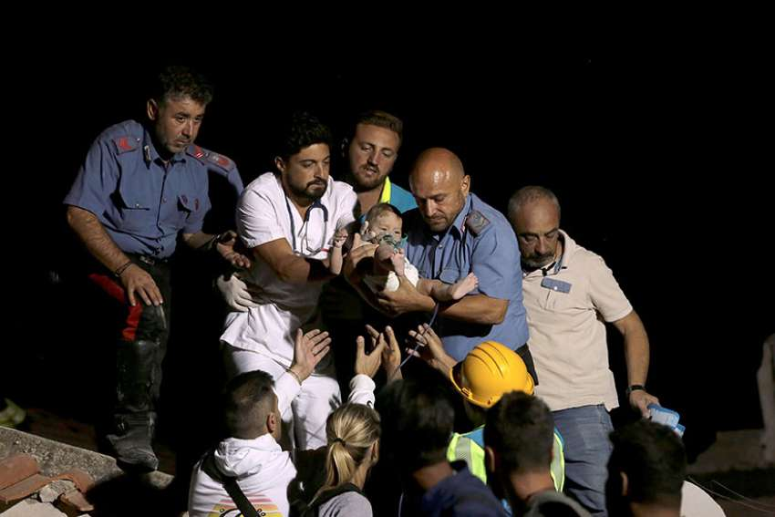 A doctor and an officer from the Italian Carabinieri police force carry a child Aug. 22 after an earthquake hit Ischia, Italy. The earthquake rattled the Italian resort island at the peak of tourist season the evening of Aug. 21, killing at least two people and trapping others under collapsed homes.