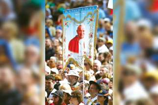 A pilgrim holds a banner showing St. John Paul II during an April 28 Mass of thanksgiving for the canonizations of new Sts. John Paul and John XXIII in St. Peter's Square at the Vatican. Divine Mercy was the key to the late pope's teaching.