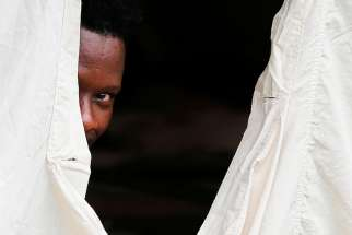 A Haitian refugee takes shelter in a tent set up by the Canadian Armed Forces near Lacolle, Quebec, Aug. 10.