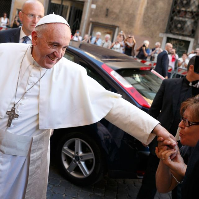 A woman kisses Pope Francis' hand as he arrives to celebrate a private Mass at the Church of the Gesu in Rome July 31.