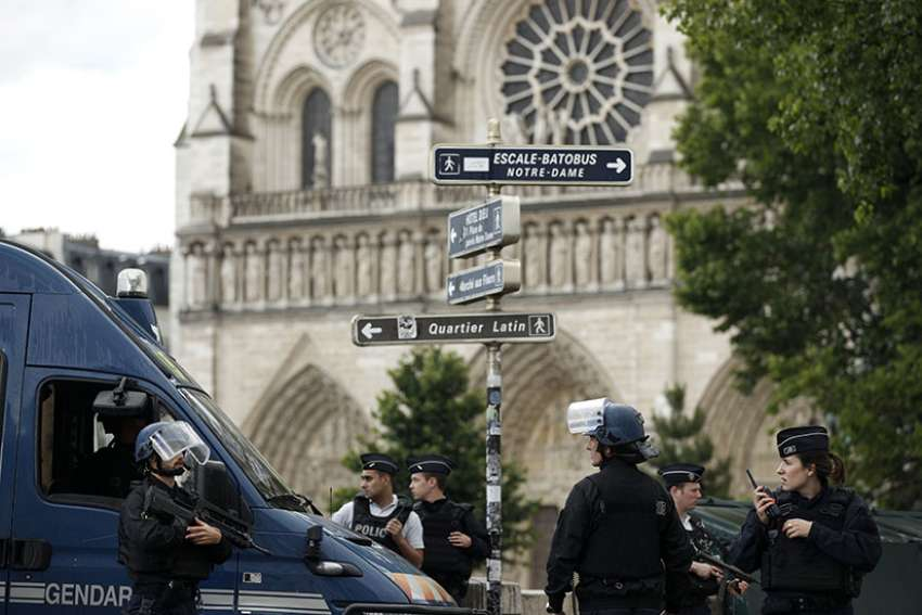 Police officers establish a security parameter outside Notre Dame Cathedral in Paris June 6 after police shot and injured a man who attacked officers with a hammer in the square outside the church.