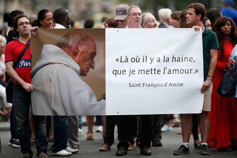 "People hold a banner with a picture of French priest Father Jacques Hamel, which reads, ""Where there is hatred, let me sow love,"" after a July 27 Mass at the Notre Dame Cathedral in Paris. Father Jacques Hamel was killed in a July 26 attack on a church at Saint-Etienne-du-Rouvray near Rouen by assailants linked to Islamic State groups."