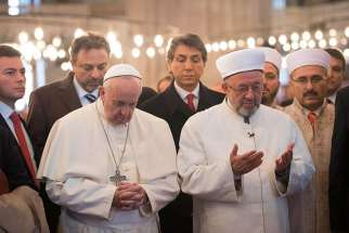 Pope Francis prays with Istanbul's grand mufti Rahmi Yaran during a visit to the Sultan Ahmed Mosque, also known as the Blue Mosque, in Istanbul Nov. 29.