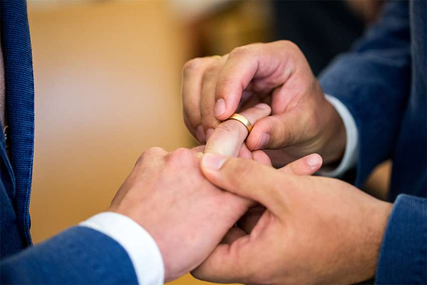 Two same-sex partners exchange wedding bands during a 2017 ceremony at the civil registry office in Munich.