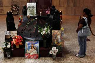 In this file photo, a tourist visits the tomb of Archbishop Oscar Romero in San Salvador.