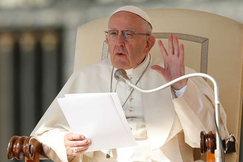 Pope Francis holds up five fingers to represent the Fifth Commandment as he speaks during his general audience in St. Peter's Square at the Vatican Oct. 10.