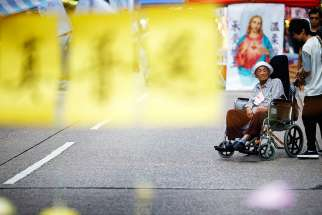 An elderly woman in a wheelchair is pushed near an improvised church in the area occupied by pro-democracy protesters in Mongkok shopping district in Hong Kong Oct. 30.