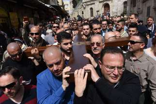 Mousa Kamar, front right, and his son, Youssef, far left corner, carry the large wooden cross during the Good Friday procession on the Via Dolorosa in Jerusalem's Old City March 25, 2016. Mousa Kamar and his sons are carrying on the tradition of his grandfather and father, carrying the cross on Good Friday.