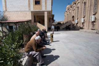 Displaced Assyrians, who fled from the villages around Tel Tamr, Syria, gather March 9 outside the Assyrian Church in Hassakeh as they wait for news about abductees remaining in Islamic State hands.