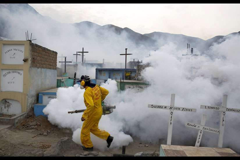 A health worker carries out fumigation as part of preventive measures against the Zika virus and other mosquito-born diseases at a cemetery on the outskirts of Lima, Peru.
