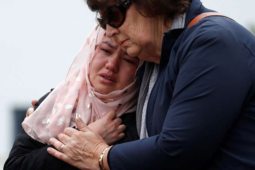 People embrace as they pay respects outside Al Noor Mosque in Christchurch, New Zealand March 18, 2019. Prayer services were held across the country and abroad after March 15 mosque attacks in Christchurch that left at least 50 people dead and 20 seriously injured.