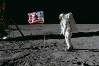 "Astronaut Edwin ""Buzz"" Aldrin, lunar module pilot of the first lunar landing mission, poses for a photograph beside the deployed U.S. flag during an Apollo 11 extra-vehicular activity on the lunar surface July 20, 1969."