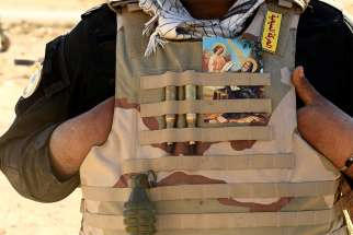 A Christian fighter displays a holy card in his vest Nov. 2016 in Mosul, Iraq.
