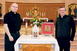Fr. Joseph Pidskalny, OSBM, left, and Fr. Gabriel Haber, OSBM, stand beside St. Josaphat's relics during the 400th anniversary celebration of the saint's order at St. Mary's Ukrainian Church in Vancouver March 25.