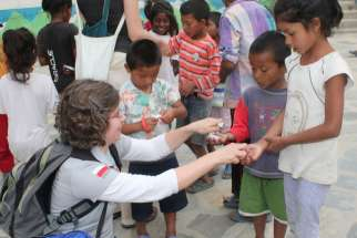 Marta Titaniec, projects coordinator of Caritas Poland, distributes sweets to inmates of the Children's Home for prisoners' children at Sankhu village outside Kathmandu, Nepal, May 7. Caritas Poland has brought a Polish air force plane with more than 14,500 kilograms of relief material for the victims of the April 25 Nepal earthquake.