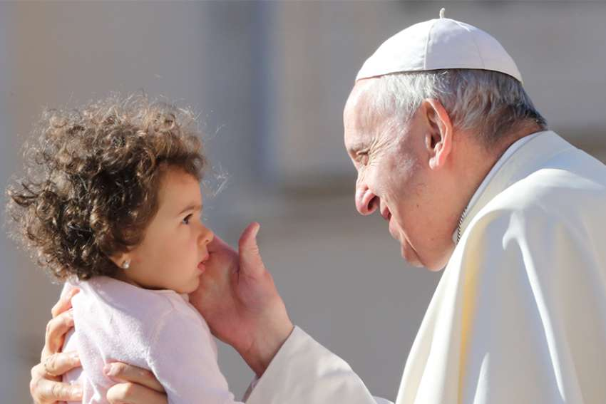 Pope Francis blesses a baby as he arrives to lead the Sept. 26 general audience in St. Peter's Square at the Vatican.