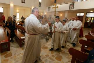 A clergyman and altar servers process during Mass July 20, 2014, at St. Joseph Chaldean Catholic Church in Baghdad, Iraq. Chaldean Christians in northern Iraq are determined to continue their 2,000-year-long mission despite the near-deadly blow inflicted by Islamic State forces and new challenges from nongovernment militias, said a priest ministering in the region.