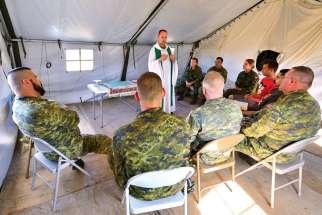 Padre Tim Nelligan, Senior Chaplain from Edmonton, presides over the holy Mass at Airfield 21 in Wainwright, Alta. Chaplains are the sounding board for soldiers who are dealing with the demons from their service.