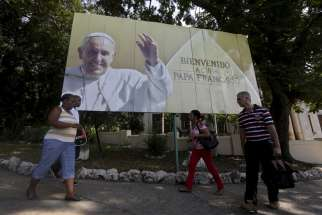 Cubans walk under a Pope Francis billboard in Havana, Sept. 14, 2015.