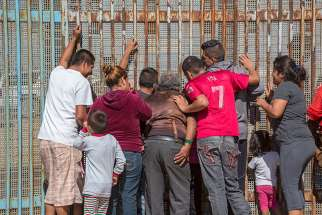 Family members in Tijuana, Mexico, separated by deportation, visit through the U.S.-Mexico border fence Oct. 16, 2016. U.S. bishops have varying opinions on providing sanctuary.