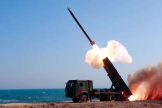 A rocket is launched during a demonstration of a new large-calibre multiple rocket launching system in this undated file photo released by North Korea's Korean Central News Agency.