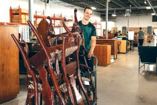 A worker has some chairs on the move at the Furniture Bank, where they deal with helping needy families all year round.