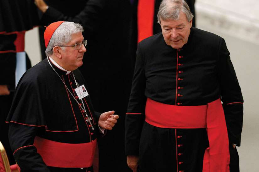 Cardinal Thomas Collins of Toronto and Australian Cardinal George Pell, prefect of the Vatican Secretariat for the Economy, talk after an event marking the 50th anniversary of the Synod of Bishops in Paul VI hall at the Vatican Oct. 17.