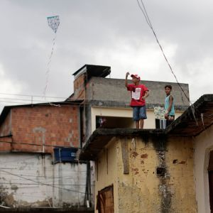 A boy flies a kite from the roof of the chapel in the Varginha sector of the Manguinhos slums complex in Rio de Janeiro July 16. A visit to Varginha is on the itinerary of Pope Francis, who arrives in Brazil July 22 for the celebration of World Youth Day .