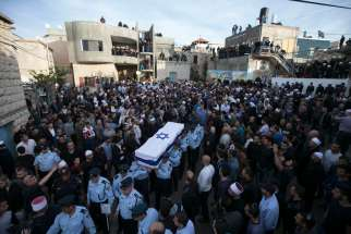 Israeli police officers carry the flag-draped coffin of Officer Zidan Nahad Seif in the northern village of Yanuh-Jat Nov. 19. Seif, a Druze, was wounded Nov. 18 while trying to stop a synagogue attack by two Palestinians armed with a meat cleaver and a gun. Four Israeli Jews with dual citizenship were killed in the attack. Latin Patriarch denounces violence in his Christmas message.