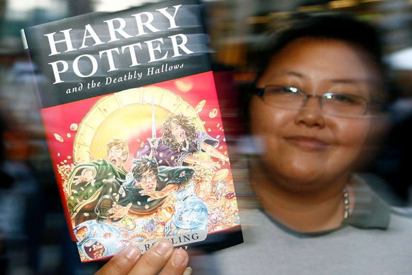 "A woman displays the last of a series of seven Harry Potter books by British author J.K. Rowling titled ""Harry Potter and the Deathly Hallows,"" in 2007 in Bangkok. June 26 was a day to remember for Harry Potter fans old and new as it marked 20 years since the iconic ""Harry Potter and the Philosopher's Stone"" was first published."