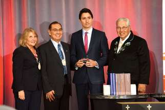 Truth and Reconciliation Commission commissioners Marie Wilson and Chief Wilton Littlechild, Prime Minister Justin Trudeau and TRC chair Justice Murray Sinclair Dec. 15 at the closing ceremony of the TRC. Trudeau was presented with a silver box containing a thumb drive of the final report.