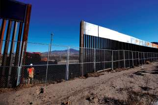 A worker stands at the U.S.-Mexico border wall at Sunland Park, N.M., opposite the Mexican border city of Ciudad Juarez.