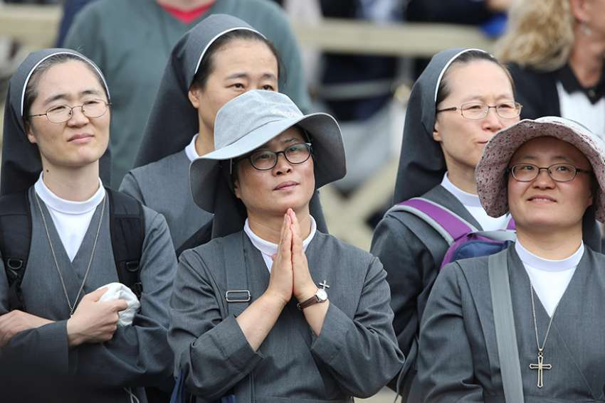 Nuns listen intently as Pope Francis leads the Angelus from the window of his studio overlooking St. Peter's Square Oct. 22 at the Vatican.
