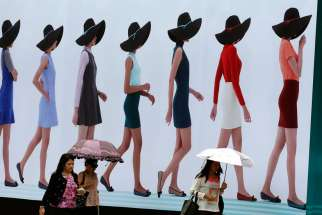 Thai women walk past a billboard in Bangkok July 28. Pope Francis prayed for all exploited women and girls during the feast of the Assumption at the Vatican Aug. 15.