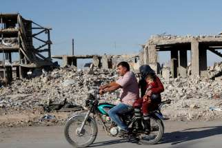 Motorists are pictured in a file photo riding a motorcycle past ruins of buildings destroyed during fighting in Kobani, Syria. Ambassadors to the Vatican from around the world were called together Oct. 15, 2020, to hear from Cardinal Mario Zenari, apostolic nuncio to Syria, about the humanitarian disaster there.