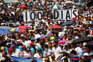 "Opposition supporters hold letters to build a banner that reads ""100 days"" during a July 9 protest against Venezuelan President Nicolas Maduro's government in Caracas."