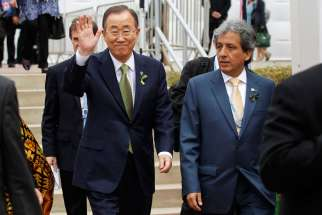 "U.N. Secretary-General Ban Ki-moon waves next to Peruvian Environment Minister Manuel Pulgar-Vidal as they arrive for the opening of the U.N. Climate Change Conference in Lima, Peru, Dec. 9. In a message to Pulgar-Vidal, Pope Francis said the time to solve the problem of climate change ""is running out."" He also insisted climate change is a serious moral problem."