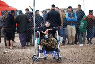 An elderly woman from Mosul, Iraq, sits at a refugee camp in Khazer, Iraq. Refugee advocates are demanding the federal government clear the refugee backlog.