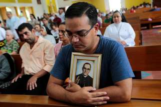 A man holding a portrait of St. Oscar Romero prays during an Oct. 13 Mass at the Metropolitan Cathedral in Managua, Nicaragua.
