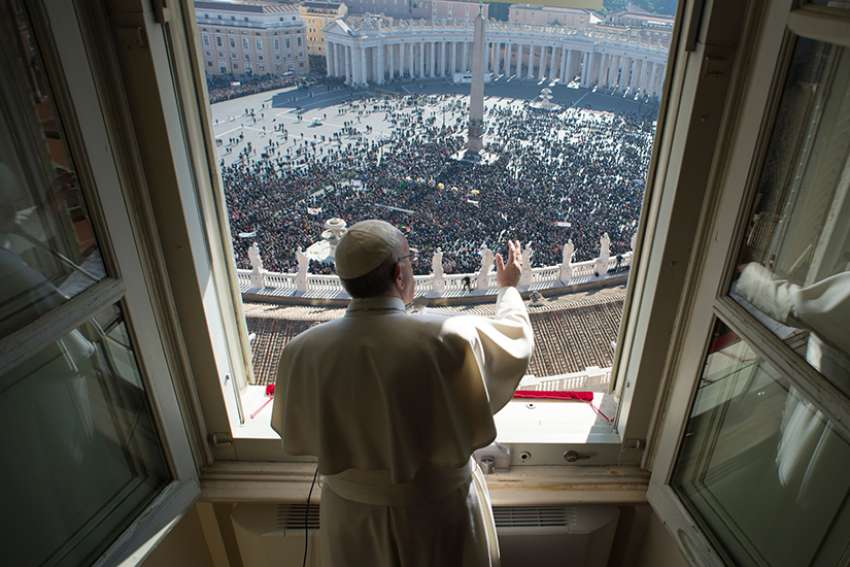 Pope Francis greets the crowd as he leads the Angelus from his studio overlooking St. Peter's Square at the Vatican Jan. 29.