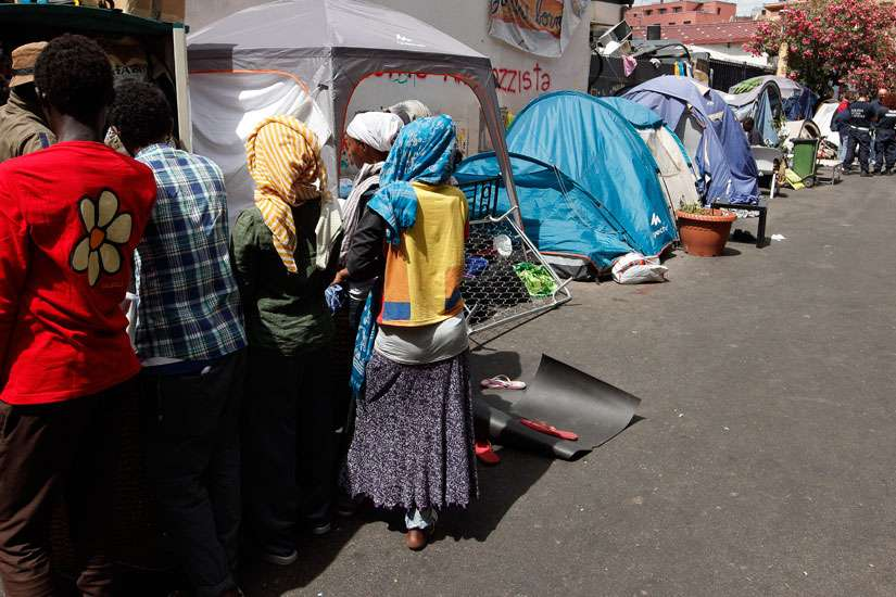 African refugees wait to receive clothing near tents where they dwell temporarily on a street in Rome July 14. A papal think tank is convening to tackle the global refugee crisis.