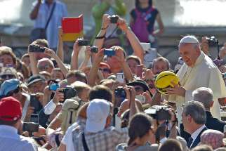 Pope Francis holds a sports ball that was given to him as he arrives for his weekly audience in St. Peter's Square at the Vatican Aug. 26, 2015.