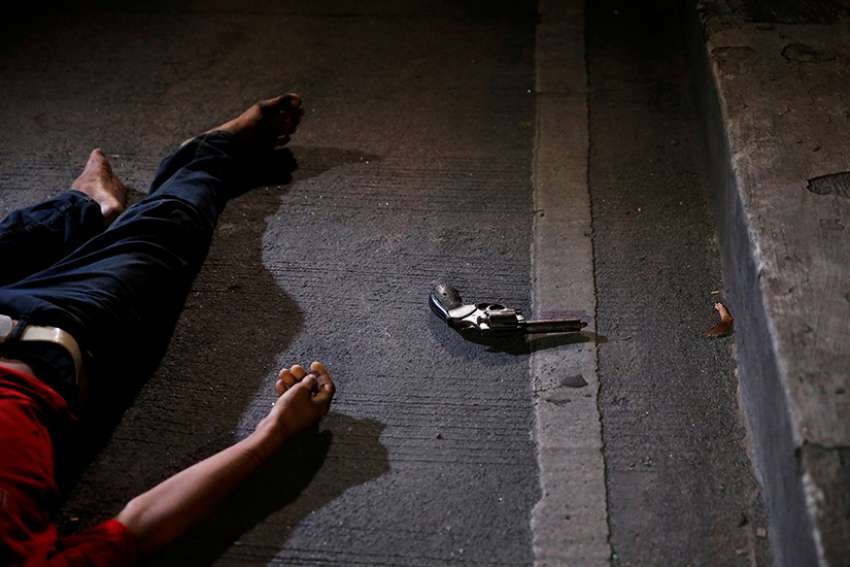 "A revolver is seen near the body of a man killed by police after drugs were found in his pockets in Manila, Philippines, Aug. 17, 2017. Catholic bishops in the Philippines broke what they described as their ""collective silence"" over ""many disturbing issues"" that have confronted the country in recent months."