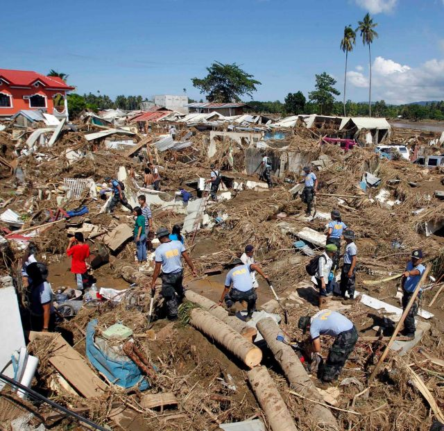 Police search for missing people in a mangled subdivision in Iligan City in southern Philippines Dec. 19. Flash floods brought on by Tropical Storm Washi left at least 650 people dead and tens of thousands homeless.