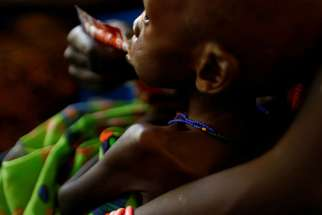 A mother feeds her child with a peanut-based paste for treatment of severe acute malnutrition at a hospital Jan. 20 in Juba, South Sudan.